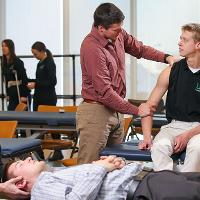 two students practicing physical therapy