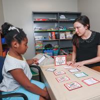 Graduate student works with child using cards.