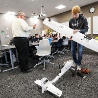 Student pieces together a model drone.