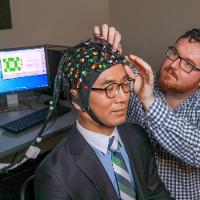 Headwear that analyzes brain functions is worn by man