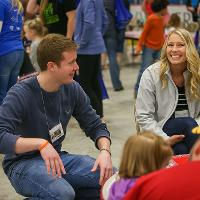 students work with students at fair