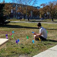 a student sitting on the grass by pinwheels in the grass