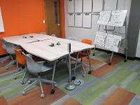 Abbott Hall 115 with new green and orange carpet, orange accent wall, new tables, chairs and a wall of portable whiteboards.