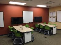 Active learning lab in the Education building.  Room has tables that seat 6 and at the end of each table is a display TV allowing students to share their work.   There area also white boards for the students to use.