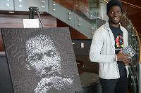 Derrick ssegawa, Vice President of the UND Black Student Association next to Portrait of Martin Luther King, Jr. created by UND student Asha Mohamoud.
