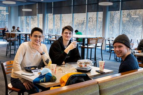 three students in Wilkerson Dining center sitting together