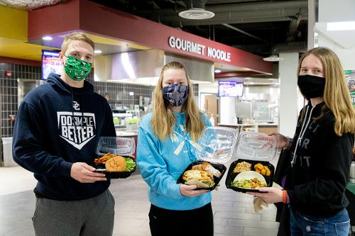 three students standing in Wilkerson Dining Center holding to-go boxes full of food