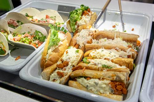 a tray with shrimp tacos and crab sandwiches ready to be served to guests