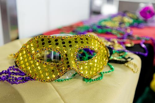 one mardi gras mask on a pile of beads on a serving table