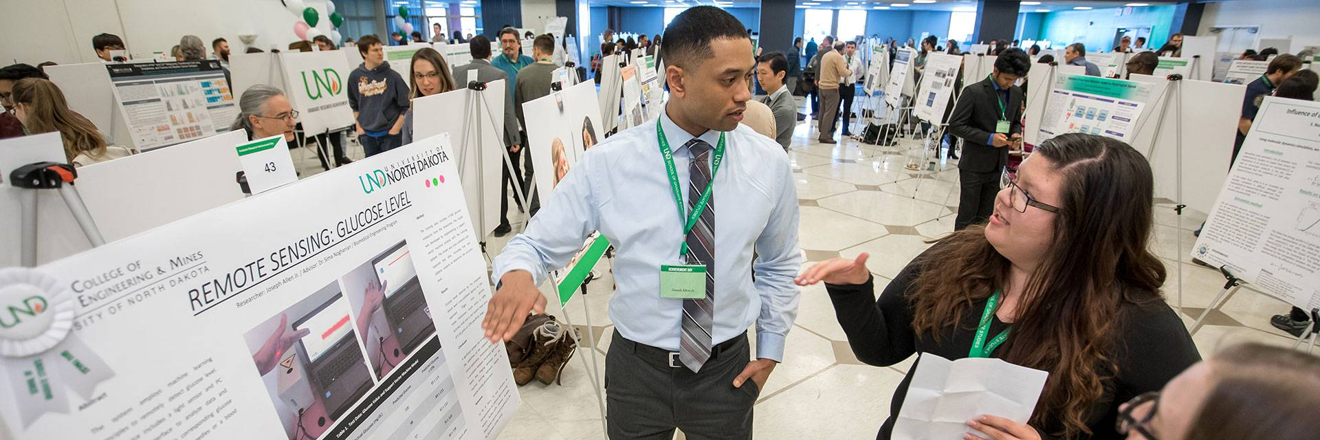 A student presents his research topic at a Graduate Expo