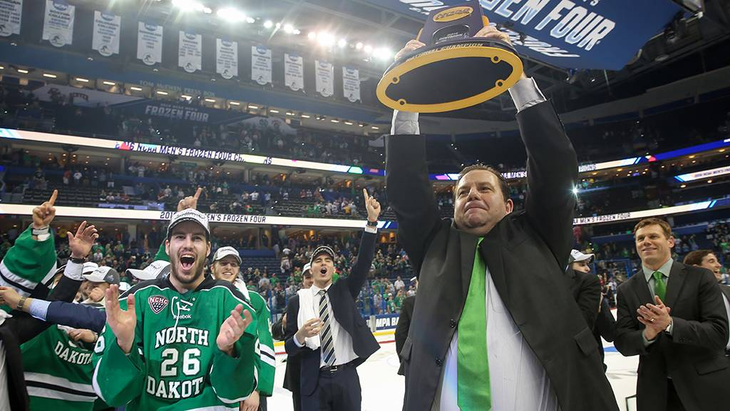 Coach Berry raising the 2016 NCAA National Hockey Trophy