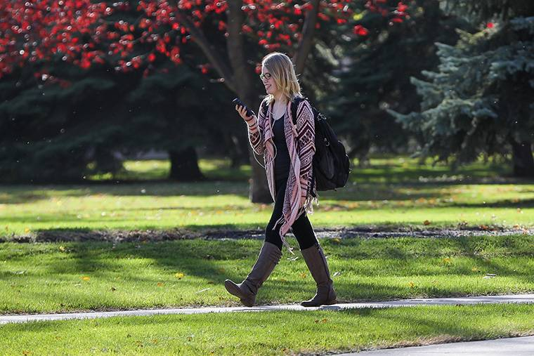woman walking on campus with cell phone