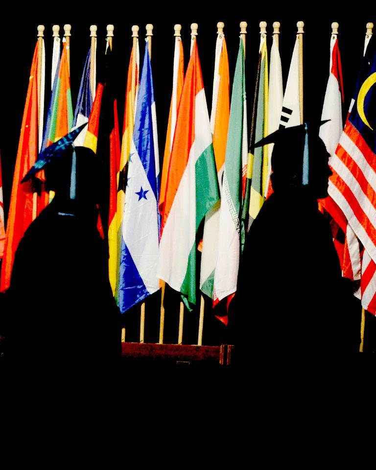 Graduates walking in front of flags