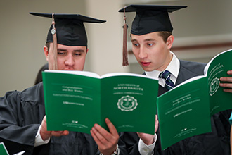 two graduates reviewing program