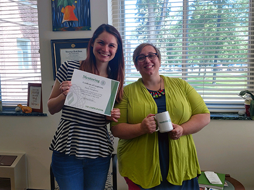 Emily Dougherty (2018 Mentee) is holding her certificate while standing next to her mentor Kayla Hotvedt.
