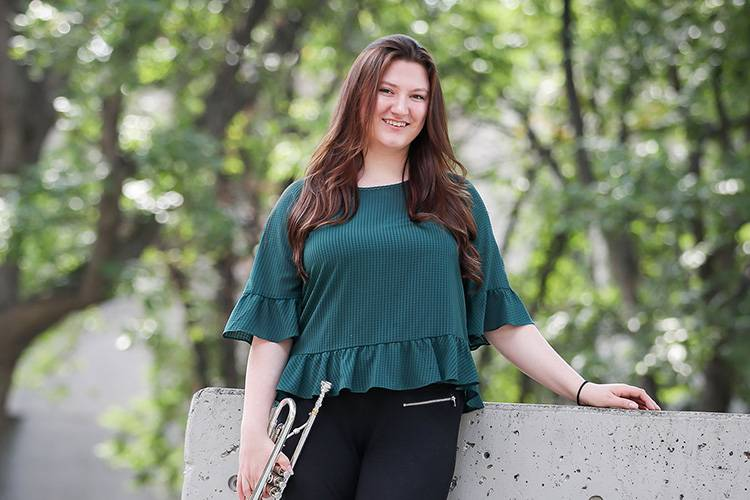 UND trumpeter Christiena leaning on wall