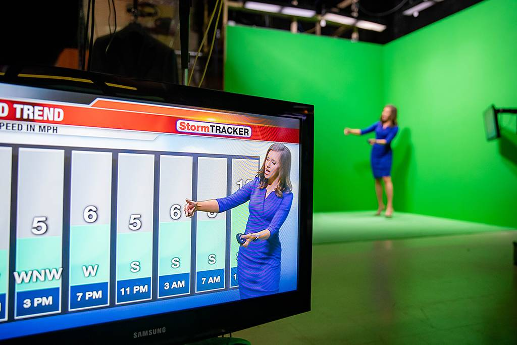Lydia Blume works in front of a green screen delivering weather
