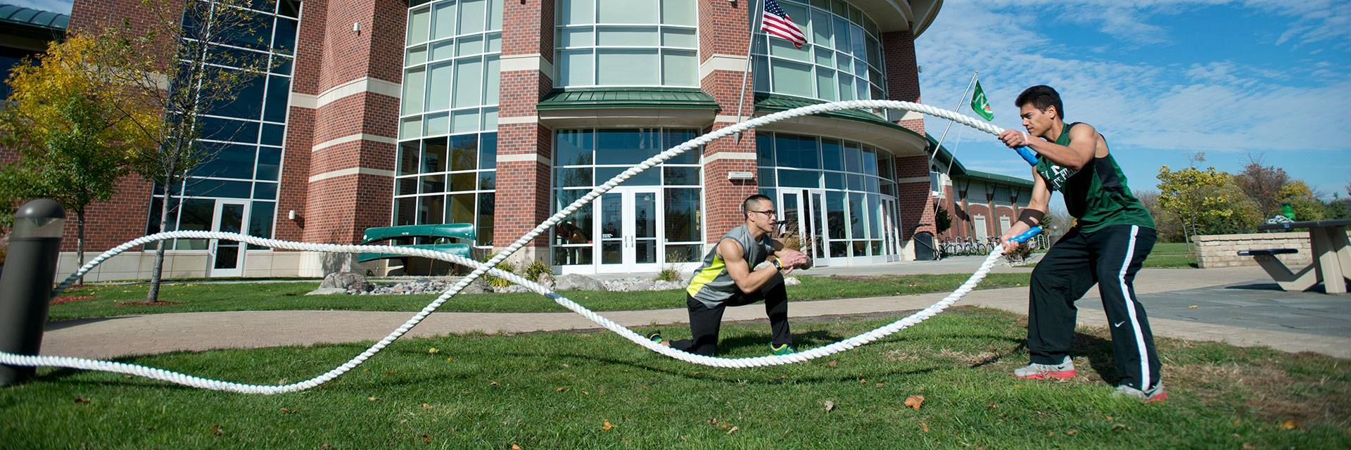 student exercising with ropes outside classroom building