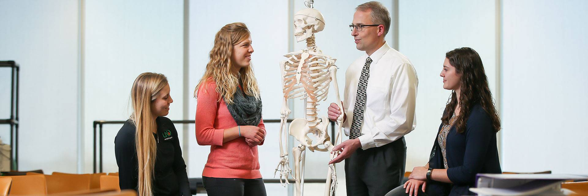 physical therapy students and instructor with skeleton