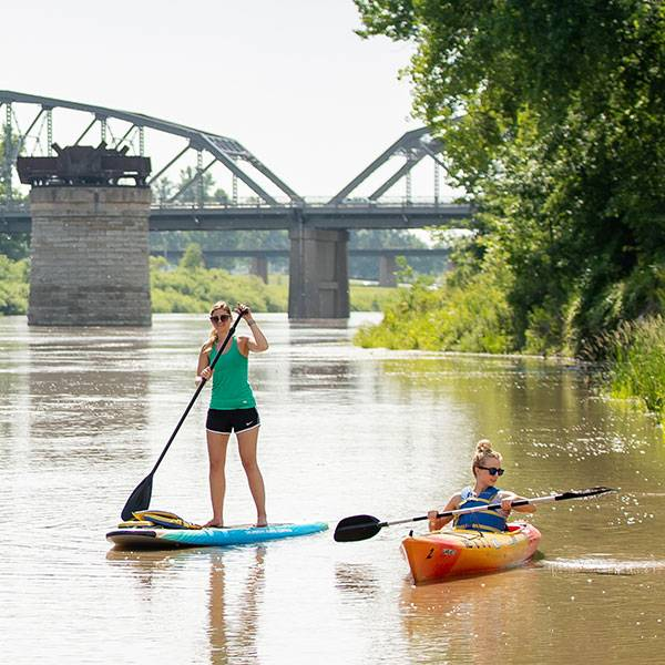 paddleboarder and kayak on red river