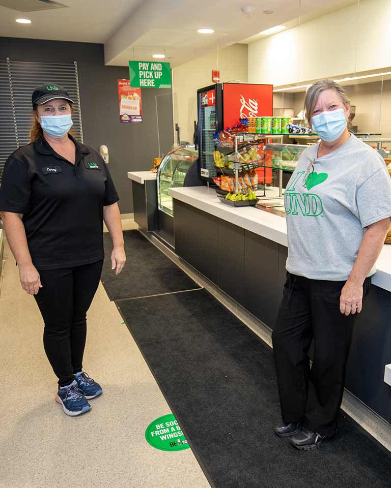 two dining employees standing in a convenience store