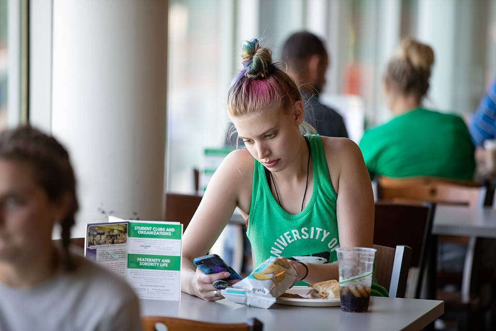 a student wearing a green tank-top sits alone at a table in the dining center on their phone
