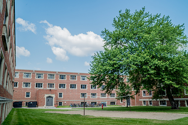 smith hall in the summer with tree & volleyball court